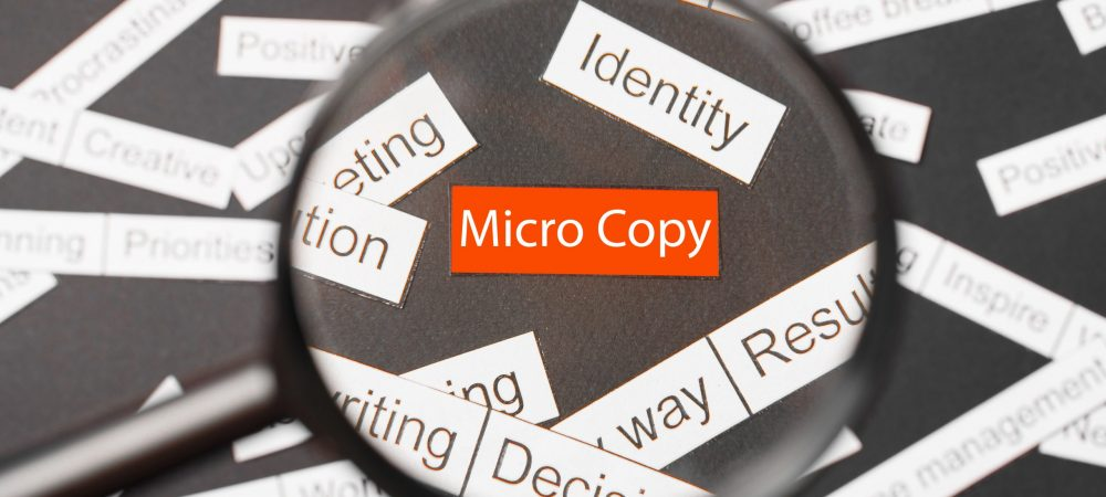Magnifier glass over the red inscription message cut out of paper. Surrounded by other inscriptions on a dark background. Word cloud concept.